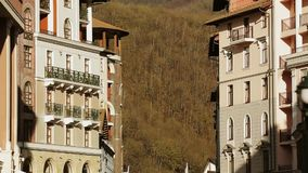 Modern buildings on street at foot of mountain. Trees. Sunny evening in city. Architecture stock footage
