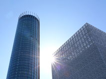 Modern buildings under the blue sky. Modern buildings against blue sky with sun rays Royalty Free Stock Photography