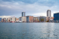 Modern buildings under cloudy sky. Izmir, Turkey. Coastal cityscape with modern buildings under overcast cloudy sky. Izmir city, Turkey Royalty Free Stock Image