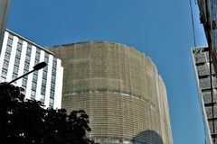 The dark post and the brightness of the building and its curves in the background. Modern buildings underneath and blue sky above them. The contrast between stock photo