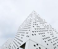Modern buildings of unusual forms from white perforated metal stock photography