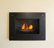 Modern built-in fireplace with fire in black color Stock Photo