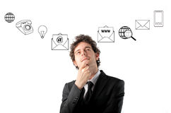 Modern business. Thoughtful businessman with symbols of communications on the background Stock Photography