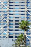 Modern business building. Glass facade and reflections and some palm trees.  Empty copy space. For Editor`s text royalty free stock photography