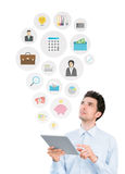 Modern business communication concept. Handsome young man holding digital tablet computer and looking on collection of mobile application icons on business and Stock Photos