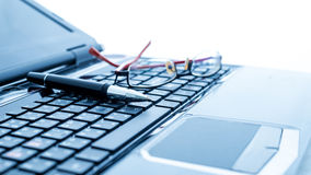 Modern business desk with laptop, pen and glasses Royalty Free Stock Photography