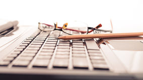 Modern business desk with laptop, pencil and glasses Stock Photography