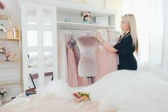 Modern business fashion designer bespoke service. Modern business. Bespoke service. Female fashion designer working in luxury showroom, selling elegant dresses royalty free stock photo