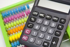 Calculator and a colorful abacus stock image