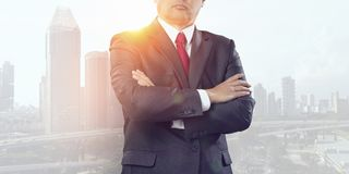 Modern business lifestyle. Mixed media. Close up of businessman with arms crossed on chest on modern city background. Mixed media Stock Photography