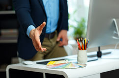 Modern business man with arm extended to handshake Stock Photography