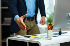 Modern business man with arm extended to handshake. Modern young business man with arm extended to handshake Stock Images