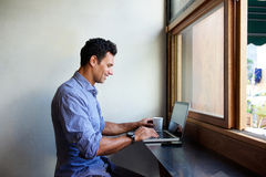 Modern business man sitting at cafe with laptop Royalty Free Stock Photos