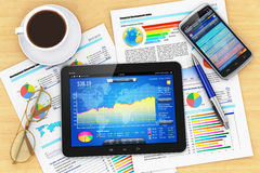 Modern office workplace. Modern business office workplace technology concept: tablet PC computer, black glossy touchscreen smartphone with stock market financial Royalty Free Stock Images