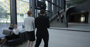 Business people at hall of office building. Modern business people walking in glass hall of office building