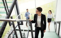 Modern business people walking on stairs in glass hall in office building Stock Photography