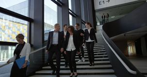 Business people at hall of office building. Modern business people walking on stairs in glass hall of office building
