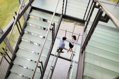 Modern business people walking on stairs in glass hall in office building Royalty Free Stock Photos