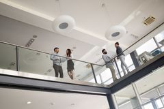 Modern business people walking on stairs in glass hall in office royalty free stock photography