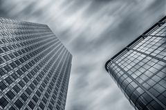 Modern business skyscrapers achitecture raising to the cloudy sk. View of business skyscrapers at a cloudy day in london, long time exposure. ideal for websites Royalty Free Stock Photography