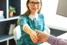 Modern business woman with arm extended to handshake Royalty Free Stock Image
