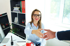 Modern business woman with arm extended to handshake. Modern young business women with arm extended to handshake Stock Photography