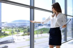 Modern business woman points to the city through the window while standing in the office.  Royalty Free Stock Photos