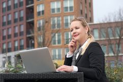 Modern business woman sitting with laptop outdoors Stock Photo