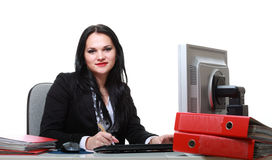 Modern business woman sitting at office desk. And smiling. Isolated Royalty Free Stock Photos