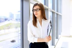 Modern business woman standing and keeping papers in the office with copy space area royalty free stock photo