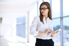 Modern business woman typing on laptop computer while standing in the office before meeting or presentation.  stock image