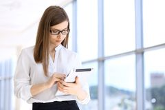 Modern business woman typing on laptop computer while standing in the office before meeting or presentation.  Royalty Free Stock Images