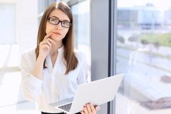 Modern business woman typing on laptop computer while standing in the office before meeting or presentation stock photos