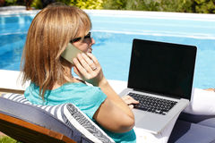 Modern business woman working at home. Modern business woman sitting at garden with phone and laptop at home. Small business royalty free stock images