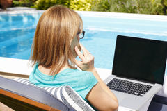 Modern business woman working at home. Modern business woman sitting at garden with phone and laptop at home. Small business royalty free stock photography