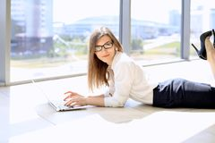 Modern business woman working with laptop computer while lying at the floor in the office, copy space.  Stock Photo