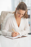 Modern business woman writing in notepad Stock Photography