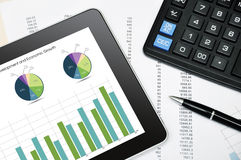 Modern business workplace. With digital tablet, calculator, pen and printed data sheet Royalty Free Stock Image