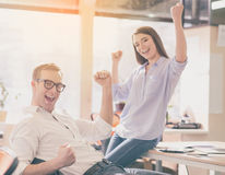 Modern business world. Hurray. Smiling and happy office workers felling very happy and being proud of themselves and their success Stock Photos
