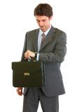 Modern businessman with briefcase checking time Stock Photos
