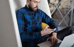Bearded hipster guy successful freelancer using cellphone and laptop computer for distance job. Modern businessman checking info on web site during video Royalty Free Stock Image