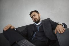 Modern Businessman. Confident Man in Suit. Modern businessman. Confident brutal man in a trendy suit looking away while sitting indoors on the sofa against the royalty free stock photography