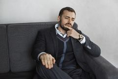Modern Businessman. Confident Man in Suit. Modern businessman. Confident young man in a trendy suit looking away while sitting indoors on the sofa against the royalty free stock photo