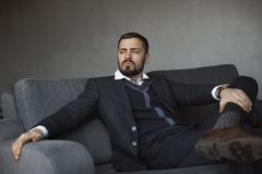 Modern Businessman. Confident Man in Suit. Modern businessman. Confident young man in a trendy suit looking away while sitting indoors on the sofa against the stock photos