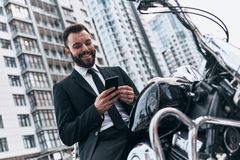 Modern businessman. Good looking young man in full suit using his smart phone and smiling while sitting on the motorbike outdoors Royalty Free Stock Photo