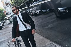Modern businessman. Handsome young man in full suit pulling his bicycle while walking outdoors Royalty Free Stock Photography