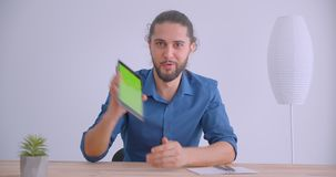 Modern businessman with ponytail turns on app on tablet and shows horizontal green chroma screen to camera in white. Office stock video footage