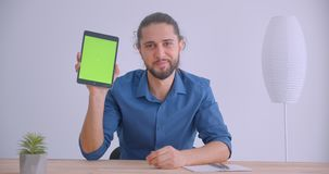 Modern businessman with ponytail working with tablet shows green chroma screen with app to camera in white office. Modern businessman with ponytail working with stock video