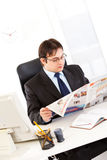 Modern businessman reading newspaper in office Stock Photos