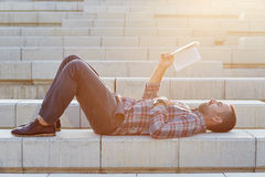 Modern businessman reading outdoors Royalty Free Stock Images